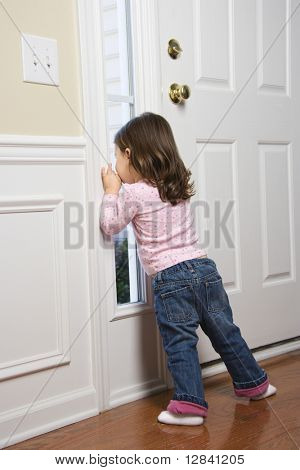 Caucasian girl toddler peeking out of window by door.