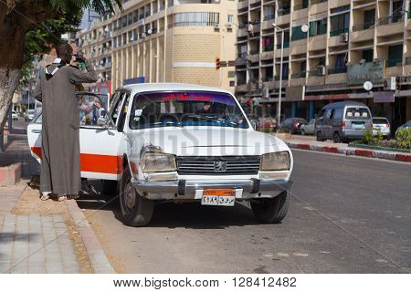 ASWAN, EGYPT - FEBRUARY 5, 2016: People entering old Peugeot 504 taxi at street.
