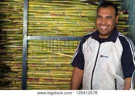 ASWAN, EGYPT - FEBRUARY 5, 2016: Local vendor smiling in front of the sugar cane juice shop.