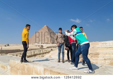 CAIRO, EGYPT - FEBRUARY 1, 2016: Group of local boys taking photos in front of the Great pyramid of Giza.