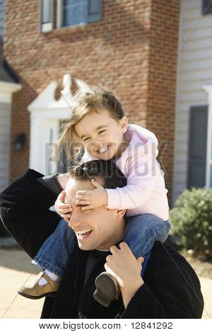 Caucasian father carrying daughter on shoulders.