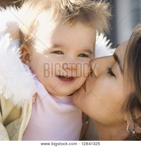 Caucasian mother holding and kissing smiling baby girl.