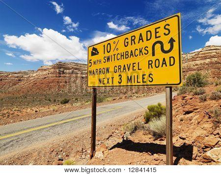 Road sign warning steep grade in Utah mountainous area.