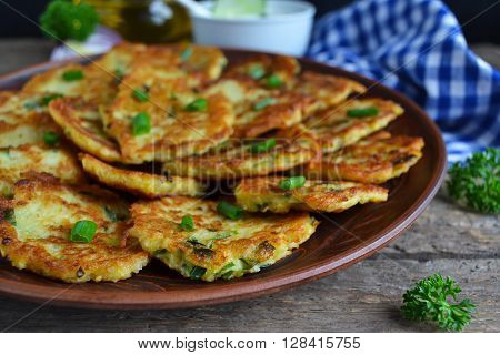 potato pancakes with green onions and sour cream on a wooden background ** Note: Shallow depth of field