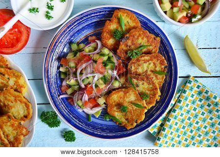 potato pancakes with vegetable salad on a blue background
