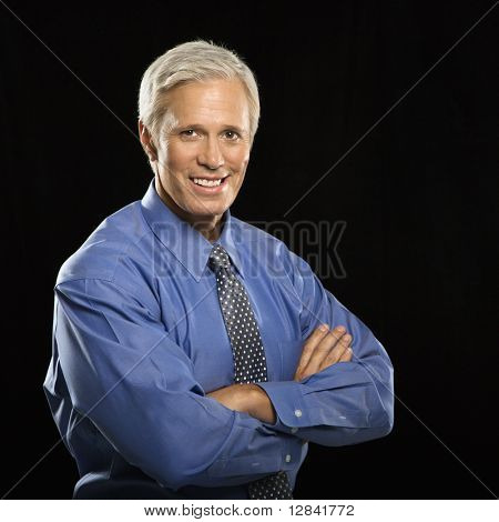 Caucasian middle aged businessman smiling at viewer with arms crossed.