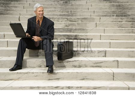Caucasian middle aged businessman sitting on steps outdoors with laptop and briefcase.