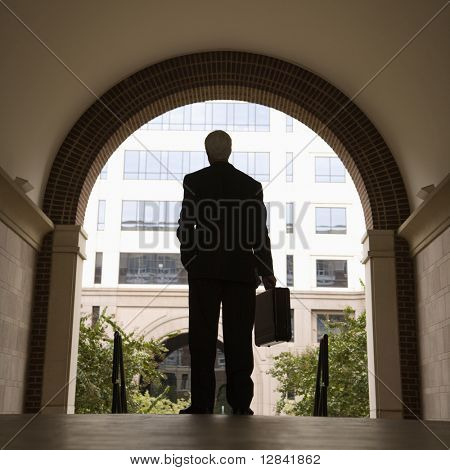 Caucasian middle aged businessman silhouette standing in archway holding briefcase.