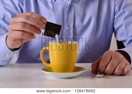 Business man pouring sugar bag on yellow coffee cup