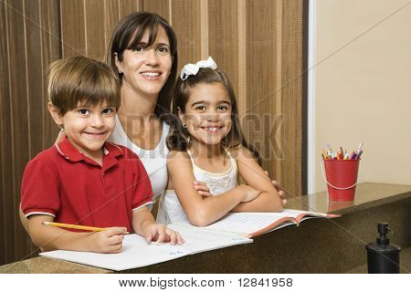 Hispanic mother and children smiling at viewer with homework.