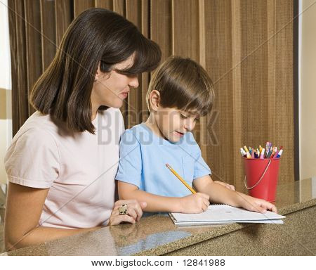 Hispanic mother helping son with homework.