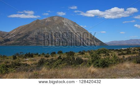 Turquoise water of Lake Ohau. Clouds over a peak of the Ben Ohau Range. Landscape in New Zealand.