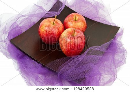 The apples lying on the plate on the purple fabric