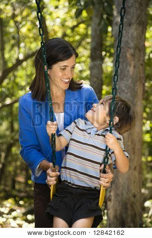 Hispanic mother pushing son on swing and making eye contact.