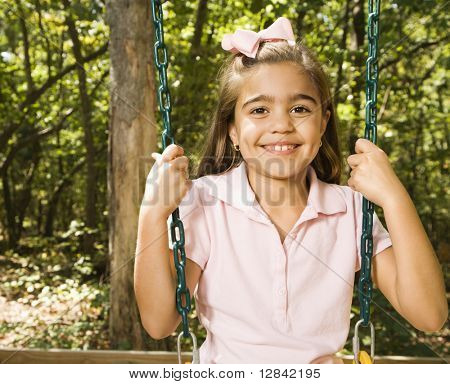 Hispanic girl sitting on playground swing smiling at viewer.