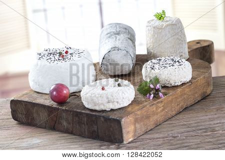 Various French  fresh goat cheese on wooden board