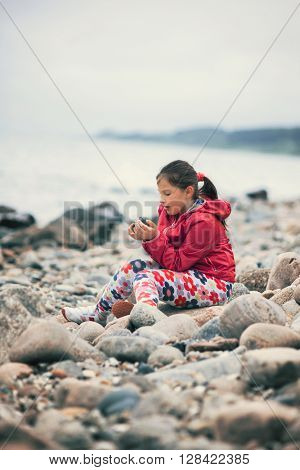 Little children beach in cold day enjoying and playing with rocks