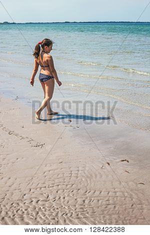 Little happy girl walking in ocean