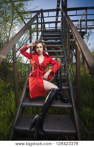 Attractive young woman alluring in sexual lingerie and red coat at grunge industrial setting. Beauty, fashion. Concept: seduction, exhibitionism.