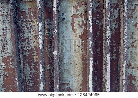 texture of the rods made of iron and old paint blue and brown on old gate