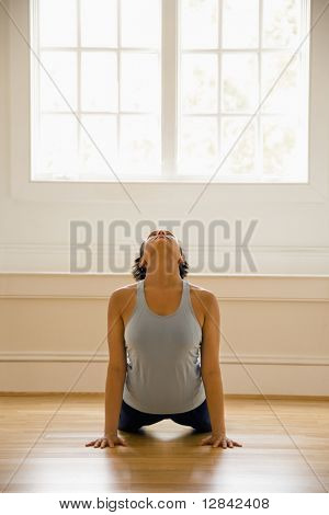 Young woman doing yoga cobra pose on wooden floor indoors by sunlit window.
