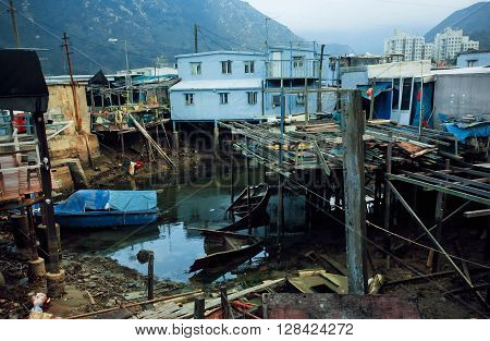 HONG KONG, CHINA - FEB 11, 2016: Poor iron houses on riverbank of fishermen village Tai O between mountains on February 11, 2016. Hong Kong dollar is the eighth most traded currency in the world.
