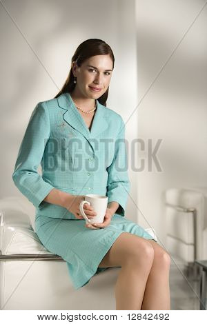Caucasian mid adult professional business woman sitting in modern office holding coffee mug looking at viewer and smiling.