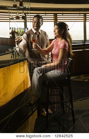 Mid adult African American man and Hispanic woman toasting at bar.