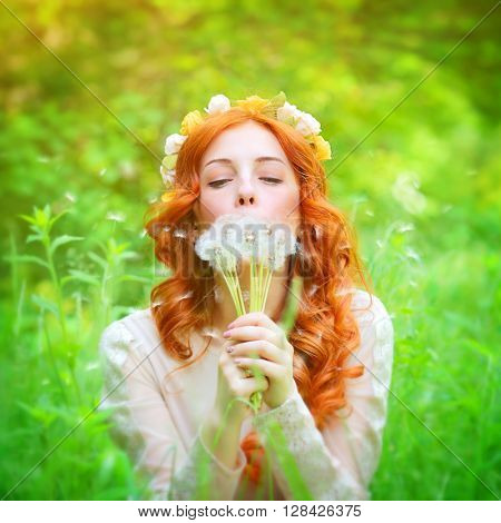 Closeup portrait of a beautiful dreamy female holding in hands dandelion flowers and with closed eyes blowing on it, enjoying beauty of spring nature