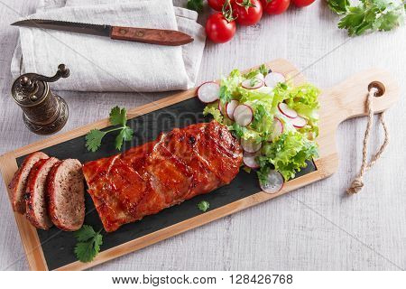 baked bacon wrapped  meatloaf with salad on the desk