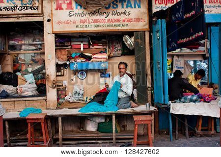 KOLKATA, INDIA - JAN 10, 2013: Tailors sew clothes in small workshops in the street of old city on January 10, 2013 in Calcutta. 15.49 perc. of the Kolkata's workforce employed in industrial and manufacturing