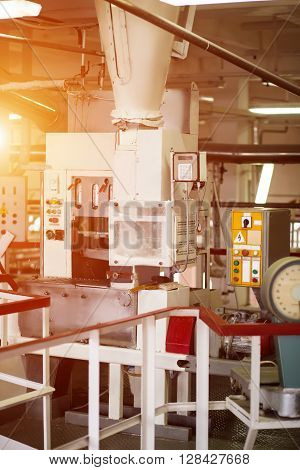 Industrial machine with control panels. Conveyor with buttons and switches. Powerful machinery at bread factory. High voltage and complex structure.