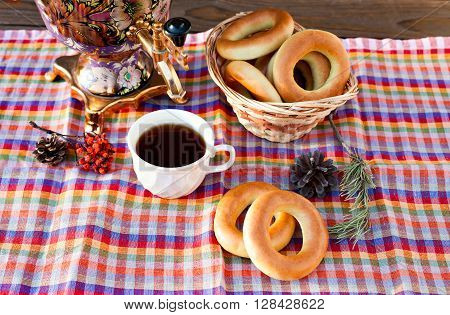 Still life with fresh cup of tea and delicious bagels in a basket. Traditional golden samovar and a sprig of mountain ash on a napkin in a cage.