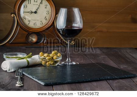 Wine glass with olives on dark wooden table