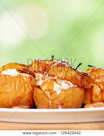 Closeup photo of a tasty baked apples stuffed with cream honey and nuts, healthy nutrition, delicious sweet food, gorgeous fruit dessert