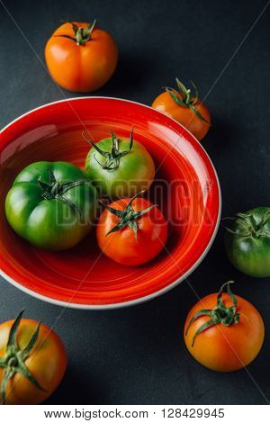 Fresh green and red tomatoes in a bowl. Fresh organic vegetables.
