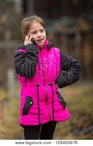 Little girl speaks by mobile phone while standing outdoors.