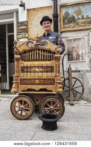Radovljica, Slovenia, EU - April 16 2016: Street performer is making music with the old music box in the streets of Radovljica, there was a chocolate festival.