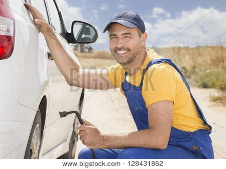 Smiling Car mechanic in uniform replaces a wheel of a stuck car in the middle of the wilderness. road services insurance concept.
