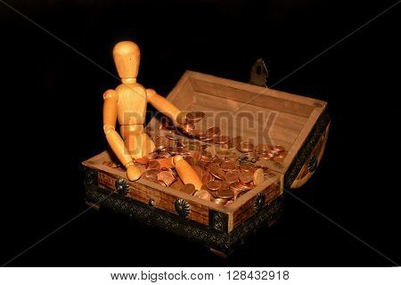 Wooden figure sitting in a wooden box with money, coin on the hand and with dark background