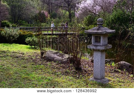 Japanese Garden in Spring. Lantern; Bridge with Two Women over a Pond; Sakura Blossom in the Background. Photo taken in Moscow Japanese Garden on April 29, 2016.