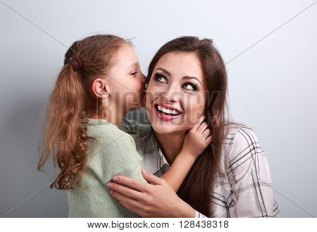 Happy Cute Kid Girl Whispering The Secret To Her Laughing Happy Mother In Ear With Fun Face On Blue