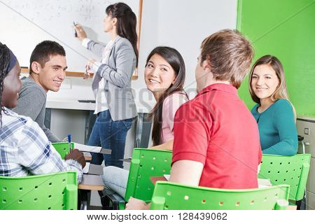 Happy high school students at math class chatting