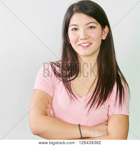 Smiling asian student crossing her arms in school