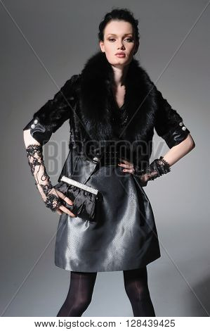 fashion model in modern clothes holding handbag posing