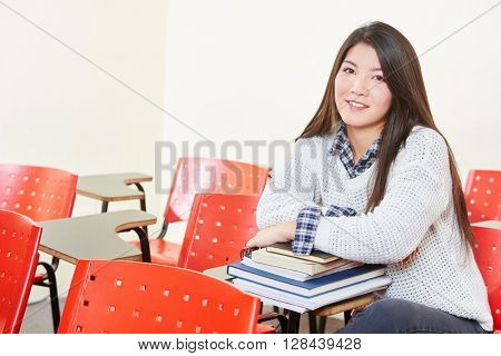 Girl with a stack of books in her classroom in high school