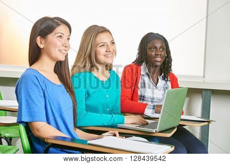 Interracial girl team working with laptop in their class