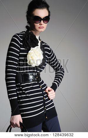 fashion girl in sunglasses with handbag posing on light background