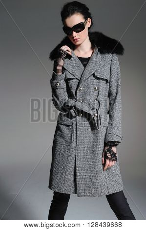 fashion model in gray coat clothes with sunglasses posing in studio