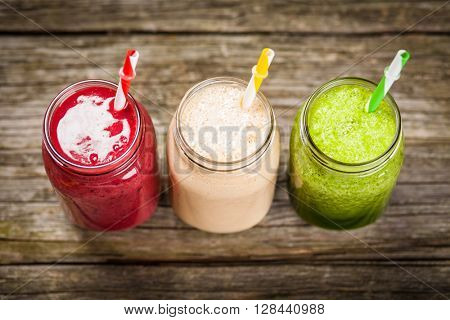 Three milkshakes and smoothies on wooden table